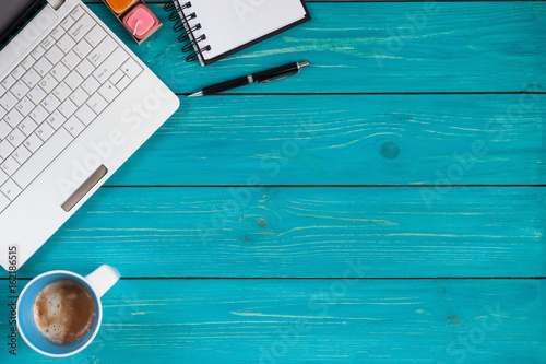 Laptop, notebook, pencil and cup of coffee on wooden background with space for text