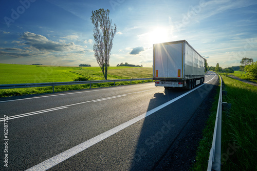 Foto op Aluminium Nachtblauw Truck driving on asphalt road along the green fields in rural landscape at sunset