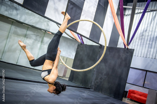 Foto auf AluDibond Gymnastik young asian acrobatic woman doing her gymnastics performance on aerial hoop or aerial ring