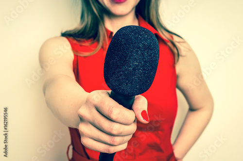 Female reporter with black microphone making interview Canvas Print