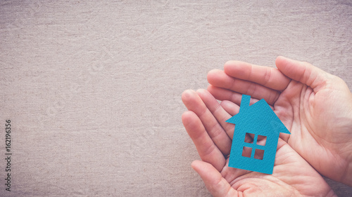 Stampa su Tela  hands holding paper house, homeless shelter and real estate concept