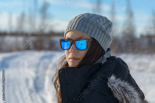 Portrait of a woman in the snow wearing sunglasses