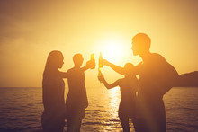 Silhouette Of People Having Party, Claging Beer Bottles At The Beach In Sunset