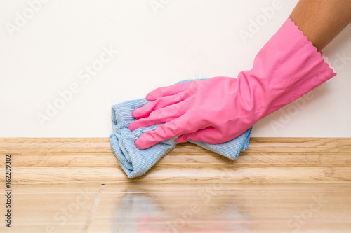 Hand in rubber protective glove cleaning baseboard on the floor from dust with rag at the wall Canvas Print