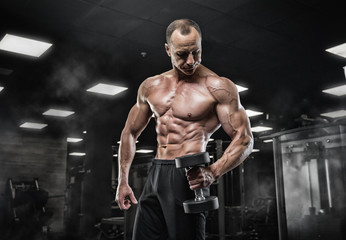 Fototapeta na wymiar Brutal bodybuilder athletic man with six pack, perfect abs, shoulders, biceps, triceps and chestBrutal bodybuilder athletic man with six pack, perfect abs, shoulders, biceps, triceps and chest