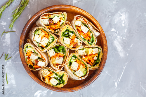Healthy vegan tofu tortilla wraps with tofu and vegetables, top view. Love for a healthy raw food concept.
