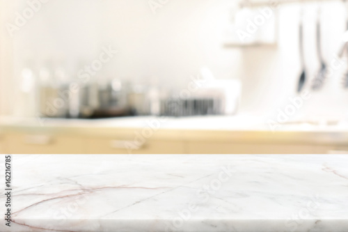 Photo Marble stone table top (kitchen island) on blur kitchen interior background