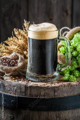 Tuinposter Bier / Cider Pint of dark beer with ingredients on old barrel