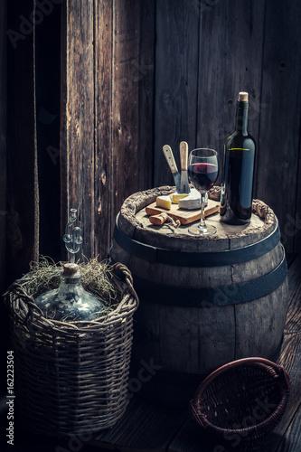 czerwone-wino-z-serem-i-balon-do-wina-w-drewnianej-piwnicy