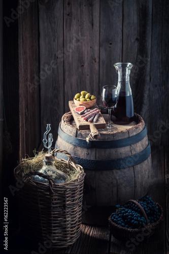 czerwone-wino-w-karafce-i-przekaski-w-drewnianej-piwnicy