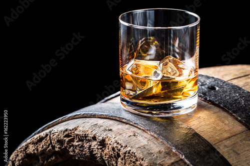 Foto op Plexiglas Alcohol Old and tasty brendy with ice on oak barrel