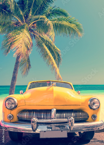 Fototapeta Classic car on a tropical beach with palm tree, vintage process