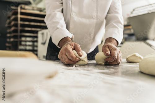 Deurstickers Bakkerij Baker kneading dough in a bakery.