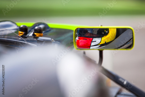 Tuinposter F1 Pilot reflected in the rearviewer of his vehicle