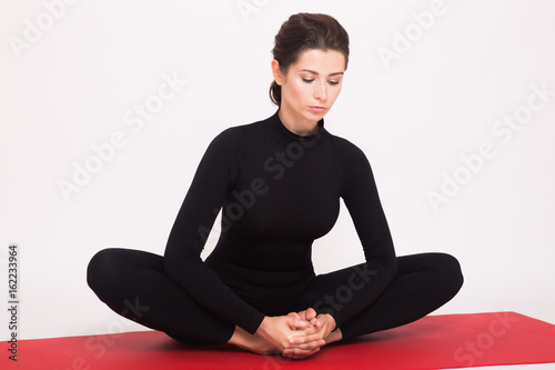 Fotografie, Obraz  Beautiful athletic girl in black suit doing yoga asanas