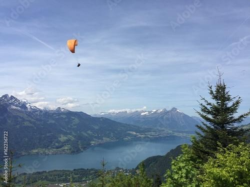 Fotobehang Bergen Paraglider Gleitschirm ob dem Thunersee Schweiz