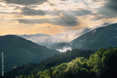 Poster de jardin Colline Mountain hill with fog and sunbeam at sunrise
