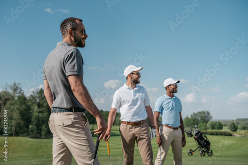 Fotografie, Obraz  young multiethnic golf players looking away while standing on pitch