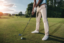 Cropped Shot Of Golfer Holding Club And Hitting Ball On Green Grass