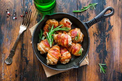 Fotografía  Oven roasted bacon wrapped chicken drumsticks in a black baking pan on the wooden rustic table, top view