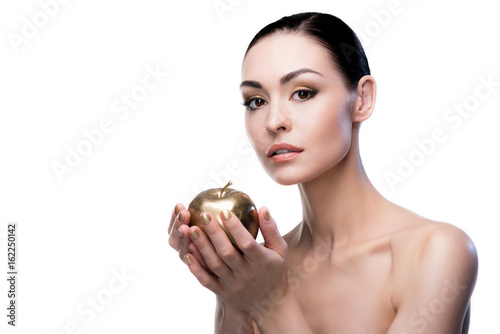 Fotografie, Obraz  caucasian lady looking at camera while holding golden apple isolated on white