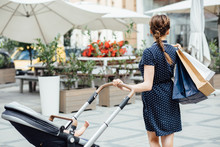 European Mother In Blue Dress With Paperbag And Baby Carriage On City Street Summer