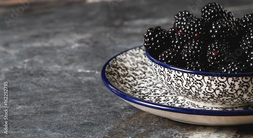 Fényképezés  Blackberry in a ceramic plate. Dark background. Sweet berry.