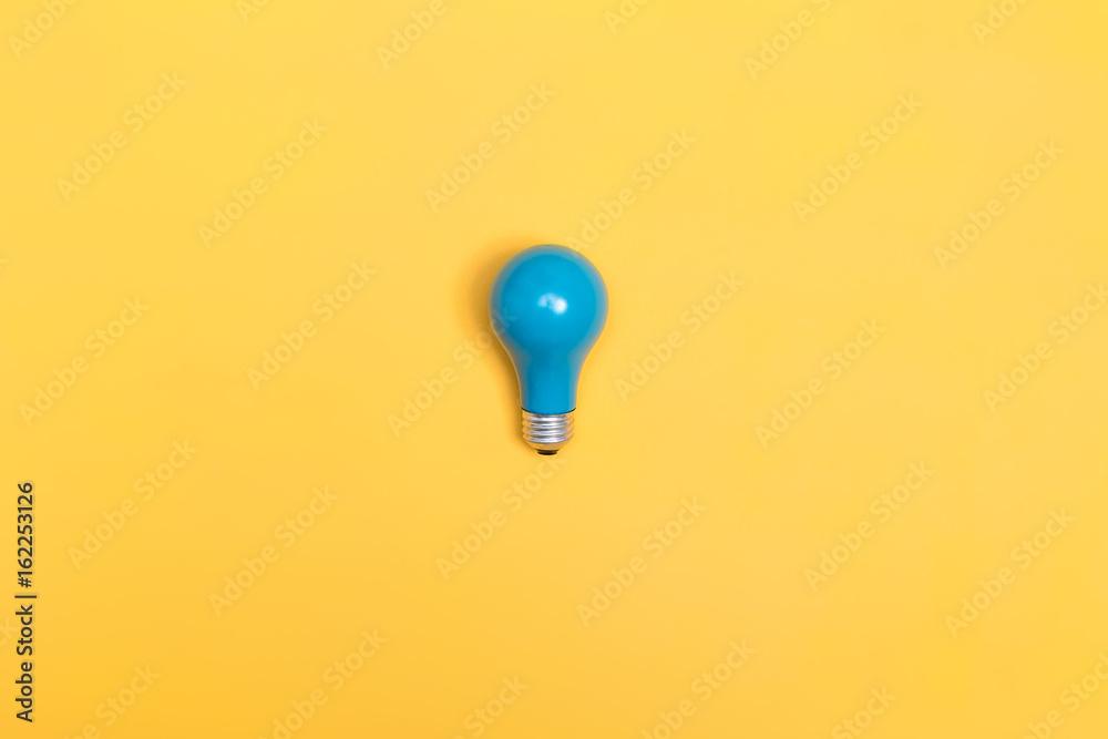 Fototapeta Blue painted light bulb on a vibrant background