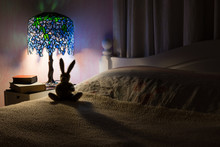 Toy Rabbit Back Lit By Tiffany Lamp In Bedroom.