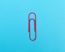 Big Paper Clip On A Bright Blue Background