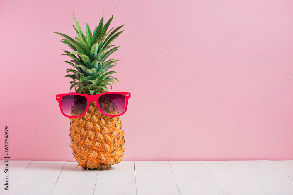 Fototapeta Funny pineapple in a sunglasses on table over pink background