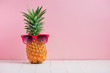 canvas print picture - Funny pineapple in a sunglasses on table over pink background