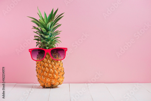 Poster Magasin de musique Funny pineapple in a sunglasses on table over pink background