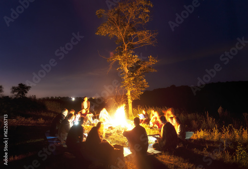 Fototapeta The company of young people are sitting around the bonfire and singing songs obraz na płótnie