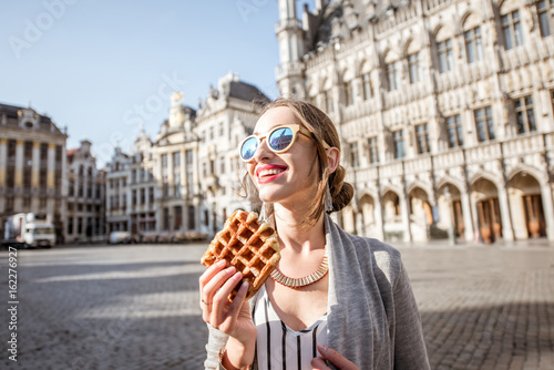 In de dag Brussel Young woman walking with waffle a traditional belgian pastry food in the center of Brussels city during the morning