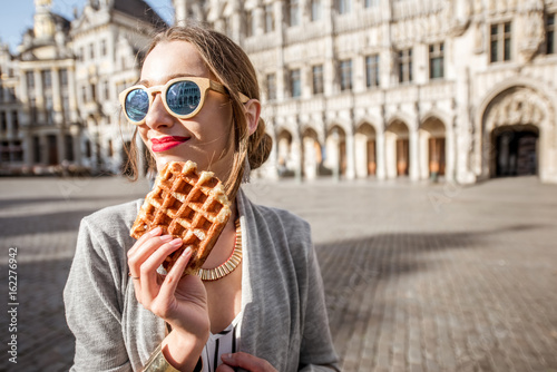Pinturas sobre lienzo  Young woman walking with waffle a traditional belgian pastry food in the center
