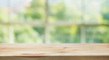 Wood Table Top On Blur Of Window Glass And Abstract Green From Garden Backgrounds