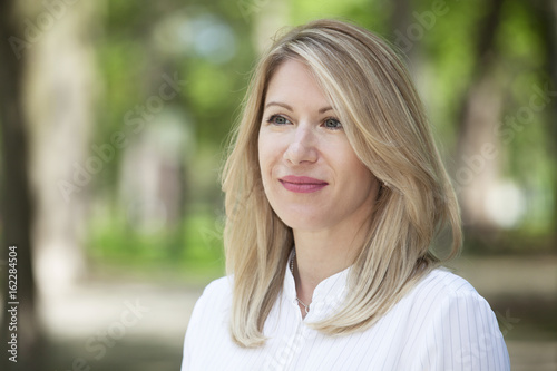 Fotografie, Obraz  Close Up Of A mature Happy Blond Woman Smiling And Looking away