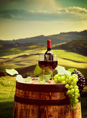 Fototapeta Do restauracji Red wine with barrel on vineyard in green Tuscany, Italy