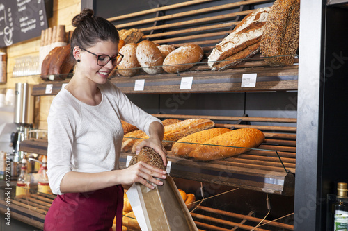 Shop assistant in bakery packing bread into a bag