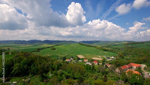 Piękne białe chmury na niebieskim niebie nad polskimi polami, górami i wsiami - 162286185