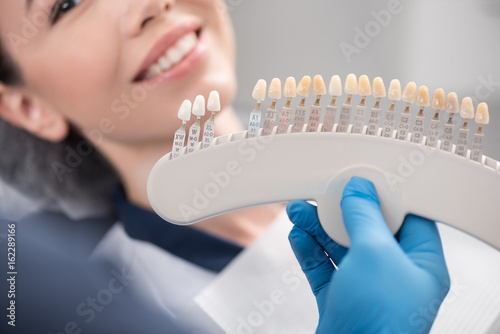 Fotografie, Obraz  Odontologist arms showing teeth implants to patient