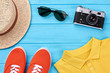 Summer vacation background, bright clothing. Hat, shoes, t-shirt, camera, sunglasses.