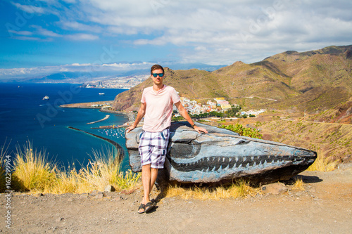 Tuinposter Canarische Eilanden Young man sitting on a cliff by the Teresitas beach on Tenerife
