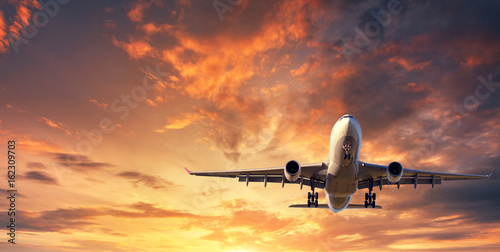 Photo sur Plexiglas Avion à Moteur Landing airplane. Landscape with white passenger airplane is flying in the blue sky with clouds at colorful sunset. Travel background. Passenger airliner. Business trip. Commercial aircraft. Concept