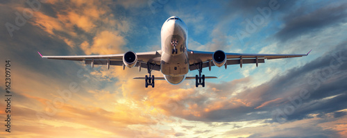 Poster Avion à Moteur Landing airplane. Landscape with white passenger airplane is flying in the blue sky with clouds at colorful sunset. Travel background. Passenger airliner. Business trip. Commercial aircraft. Concept