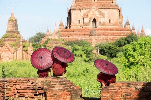 Monk children sitting in temple ruins under umbrellas