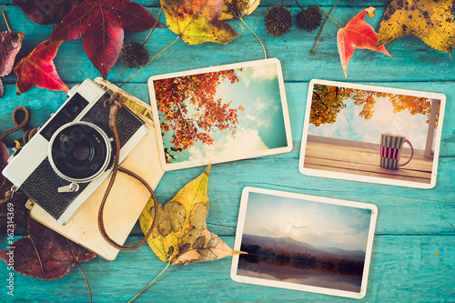 Photo album in remembrance and nostalgia in autumn (fall season) on wood table. instant photo of retro camera - vintage and retro style