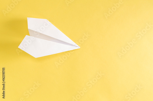Paper airplane on a bright yellow background