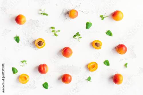 Apricot on white wooden background. Sliced apricot top view, flat lay